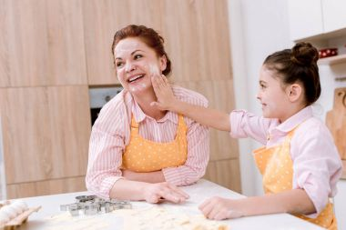 Happy grandmother and little granddaughter playing with flour at kitchen while cooking stock vector