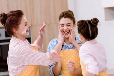 Three generations of laughing women playing with flour at kitchen stock vector