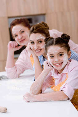 three generations of happy women in aprons with flour on faces at kitchen and looking at camera