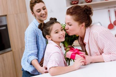 mother and grandmother presenting gift and flowers to daughter for birthday