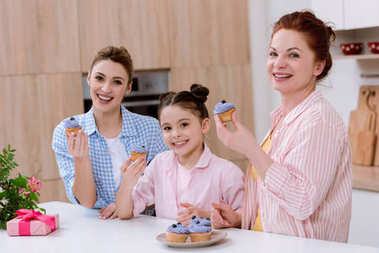 three generations of women eating cupcakes at kitchen
