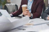 Fényképek levágott lövés építész, a papír csésze kávé dolgozó építési tervek