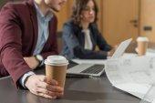 Oříznout záběr podnikatelé s papírové šálky kávy společně s přenosným počítačem v kanceláři