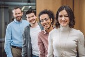 Fotografie group of successful businesspeople standing in row and looking at camera at office