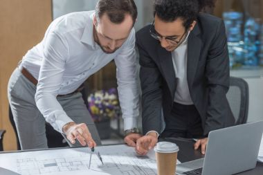 handsome architects using compass for building plans