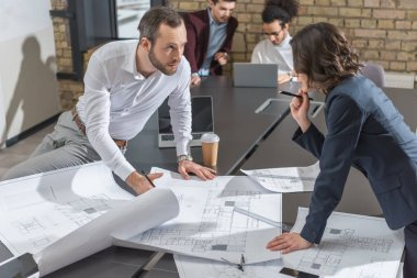 Architects working together on building plans at office stock vector