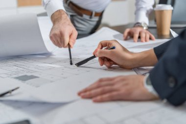 Cropped shot of architects working with building plans together at office stock vector