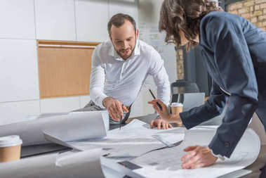 architects working with building plans together at modern office