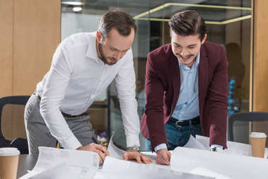 happy architects working with building plans at office