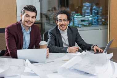Happy young architects with building plans sitting together at office stock vector