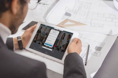 cropped shot of young architect using tablet at workplace with linkedin website on screen