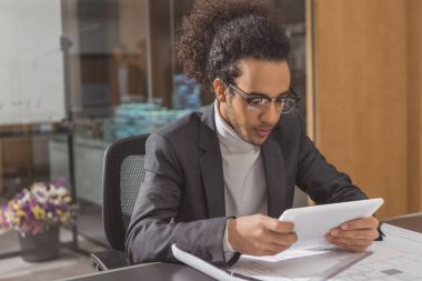 focused young architect using tablet at workplace in modern office