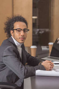 handsome young architect in suit sitting at workplace at office