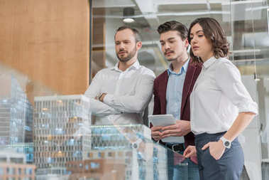 team of serious architects looking at miniature town model