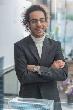 happy young architect in suit with crossed arms at office
