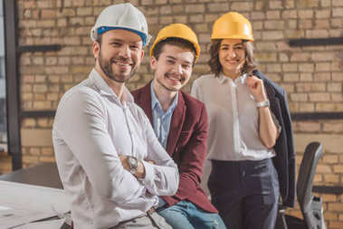 team of happy architects in hard hats looking at camera