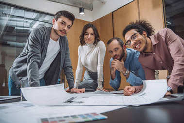 Group of successful architects discussing plans and looking at camera at office stock vector