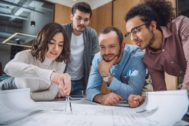 group of architects drawing building plan together at office