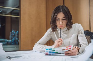 thoughtful young designer picking color from palette
