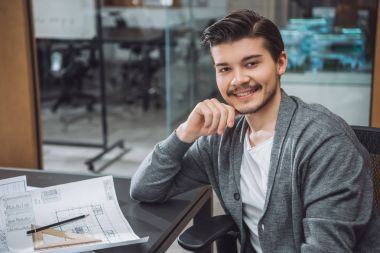 handsome young architect sitting at workplace with building plans at office