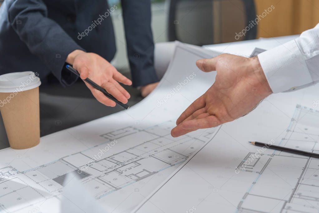cropped shot of architects discussing building plans together