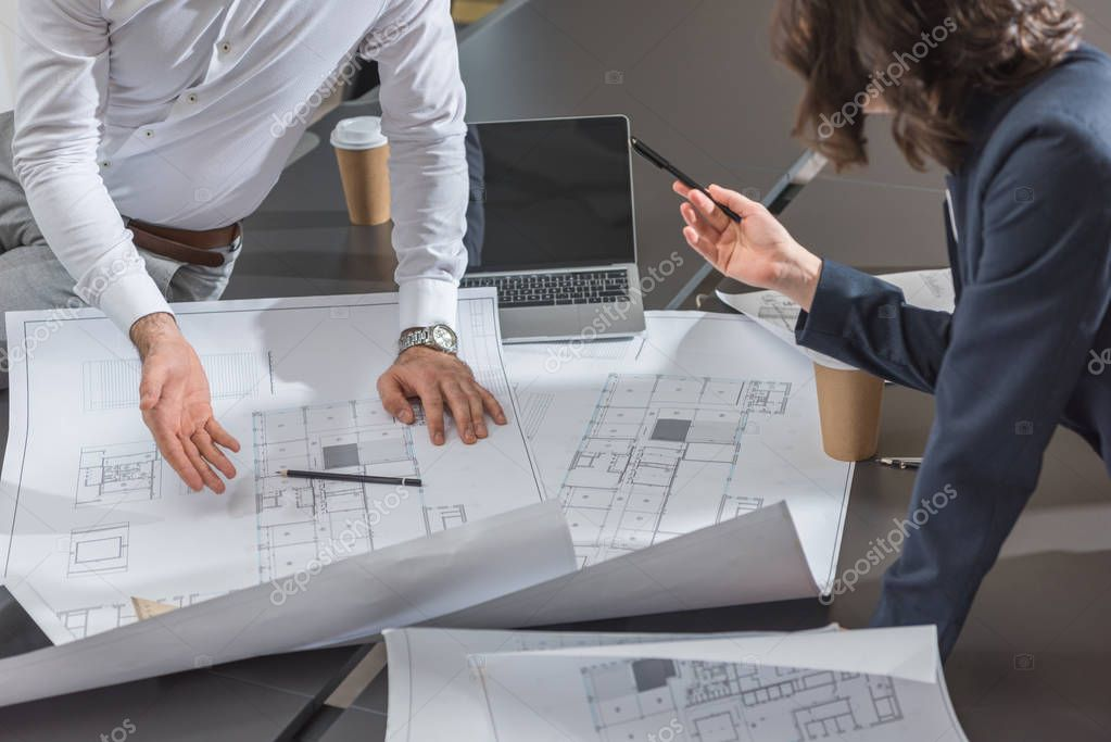 cropped shot of team of successful architects discussing building plans together