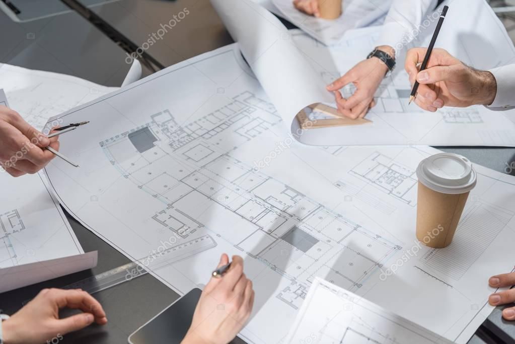 Cropped shot of team of architects brainstorming on building plans stock vector