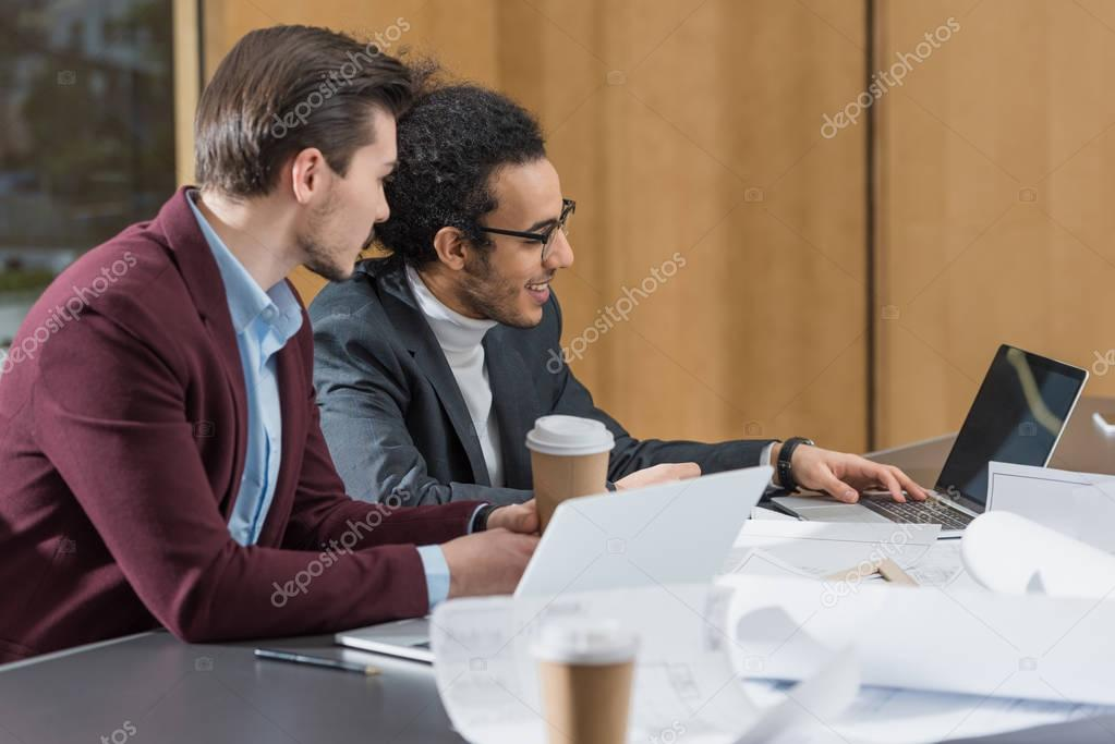happy young architects working with laptop together at office