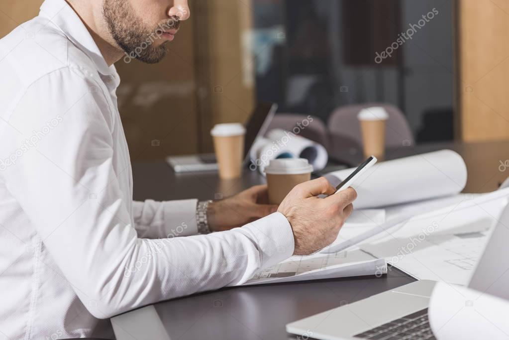 handsome architect with paper cup of coffee using smartphone at office