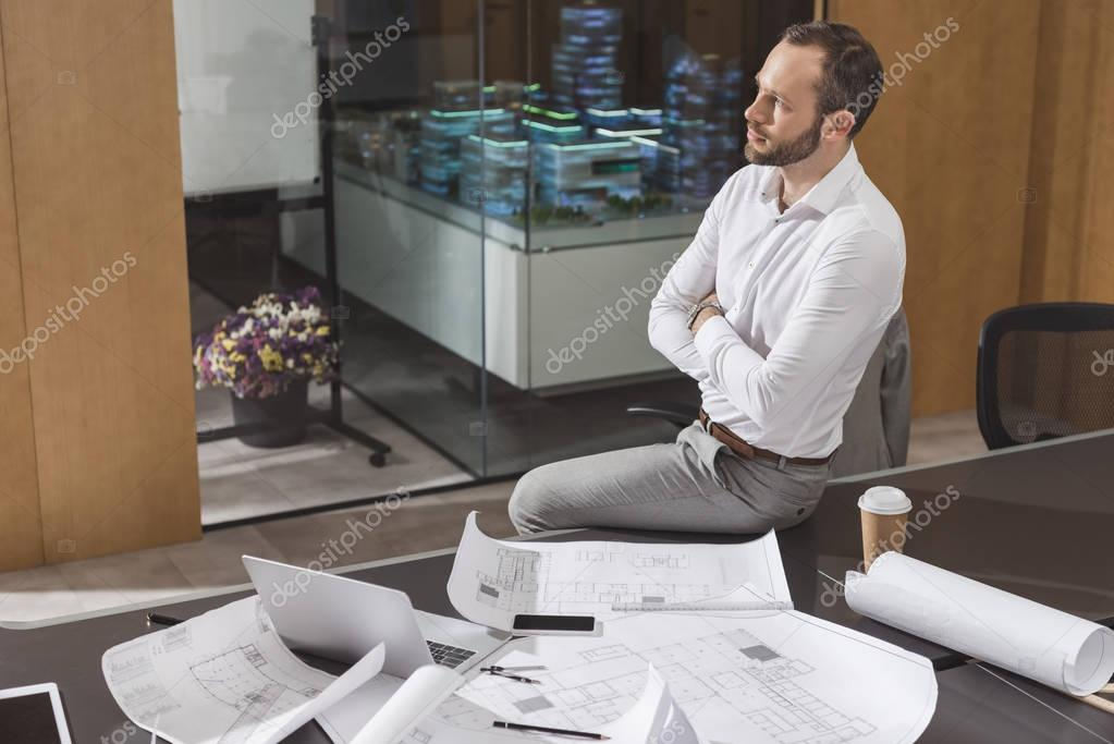 Handsome architect sitting on table with crossed arms at office