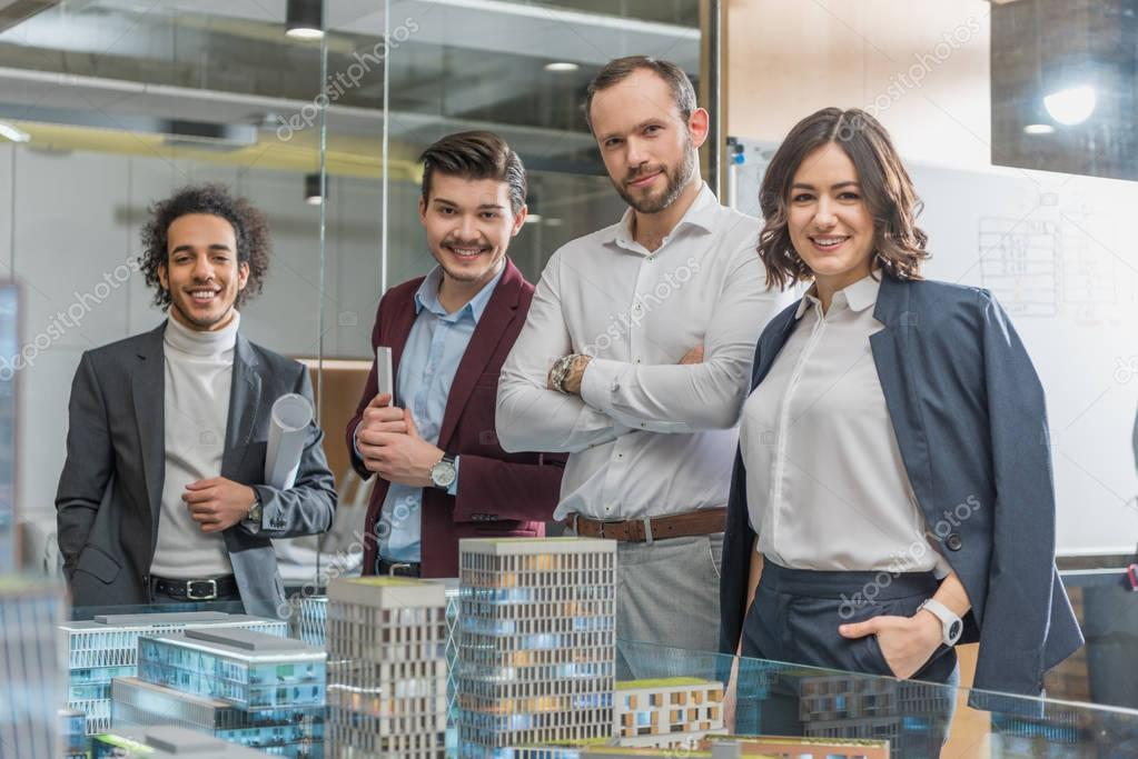 group of happy architects standing next to building models at office
