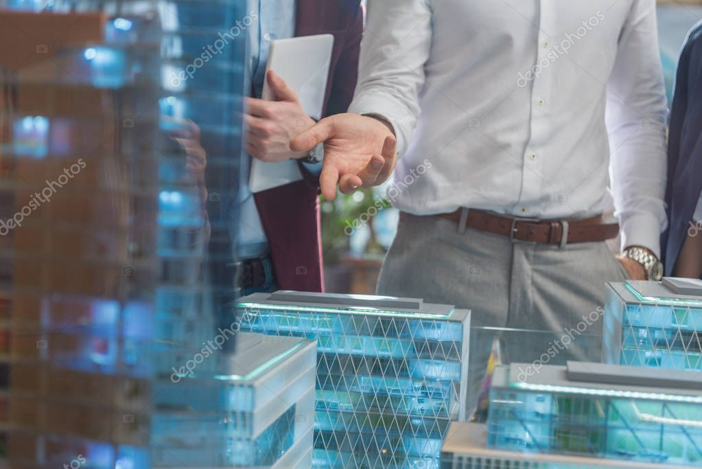 cropped shot of businessman showing miniature model of modern city to clients