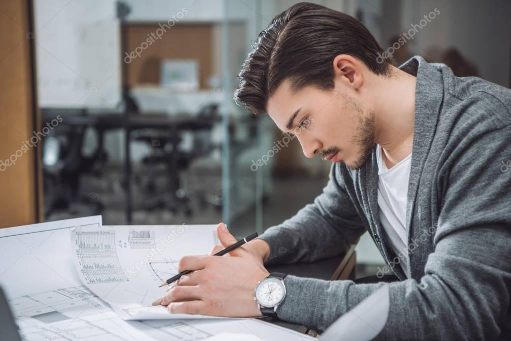 handsome young architect drawing building plans at office