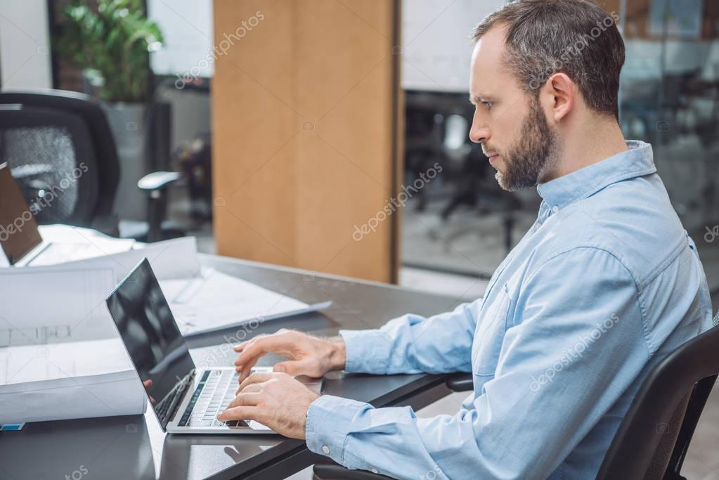 handsome focused architect working with laptop at office