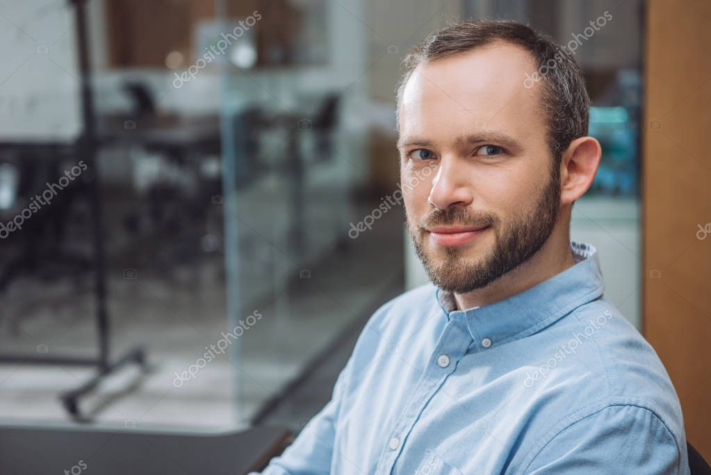 close-up portrait of handsome successful businessman at office