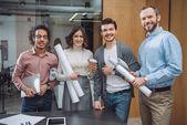 Skupina úspěšných architektů s válcované plány v kanceláři