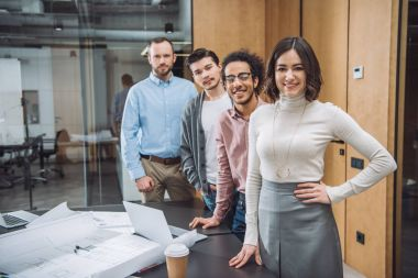 group of successful architects standing in row and looking at camera at office