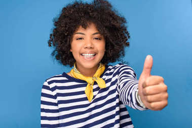 Smiling african american young girl showing thumb up, isolated on blue stock vector