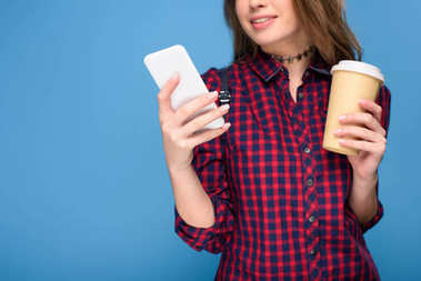 cropped view of young girl with coffee to go using smartphone, isolated on blue