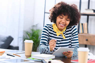 portrait of smiling african american student with notebook studying alone