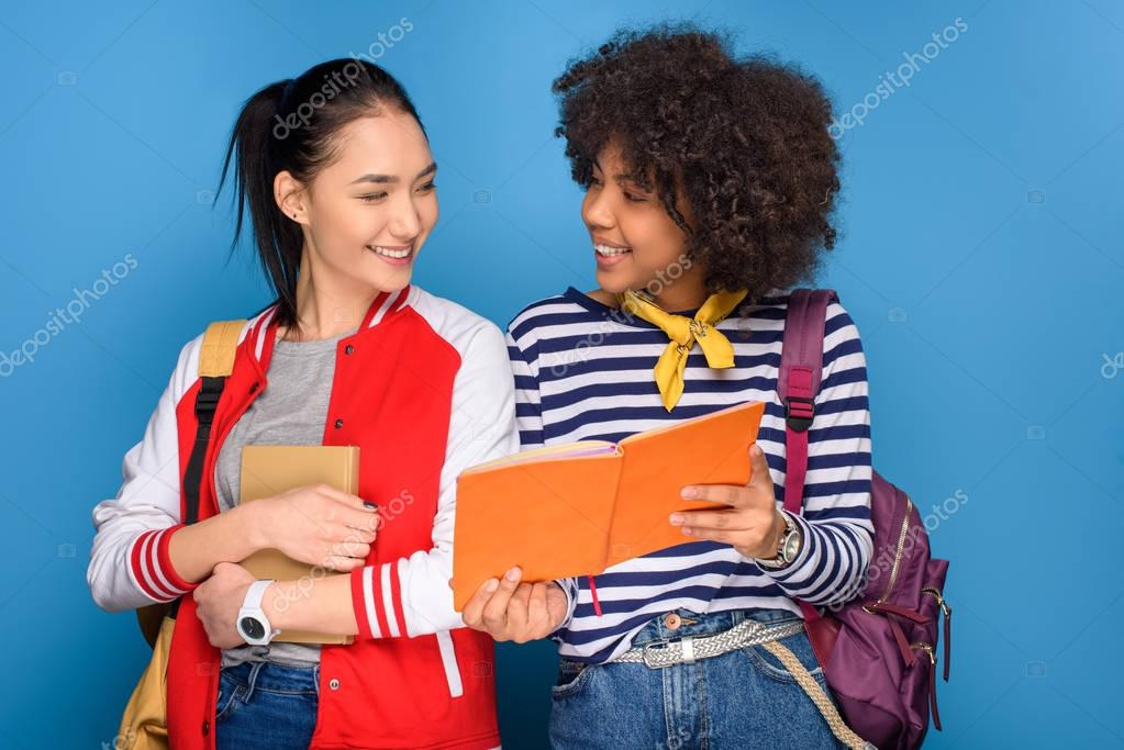 cheerful multiethnic students posing with books, isolated on blue