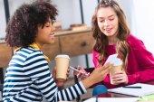 Fotografie usmívající se multikulturní studenti společně pomocí smartphonu