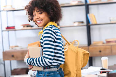 side view of smiling african american student with books and backpack