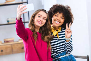 portrait of cheerful multiracial young women taking selfie together