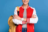 Fotografie partial view of smiling student with backpack isolated on blue
