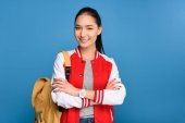 Photo portrait of smiling asian student with backpack isolated on blue