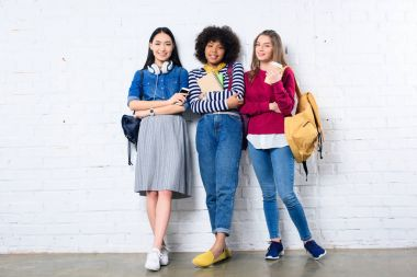 smiling multiracial students standing against white brick wall