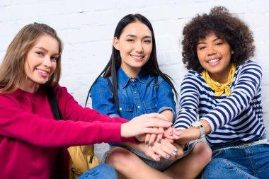 portrait of smiling multicultural students holding hands together