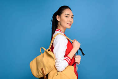 side view of pretty asian student with backpack isolated on blue