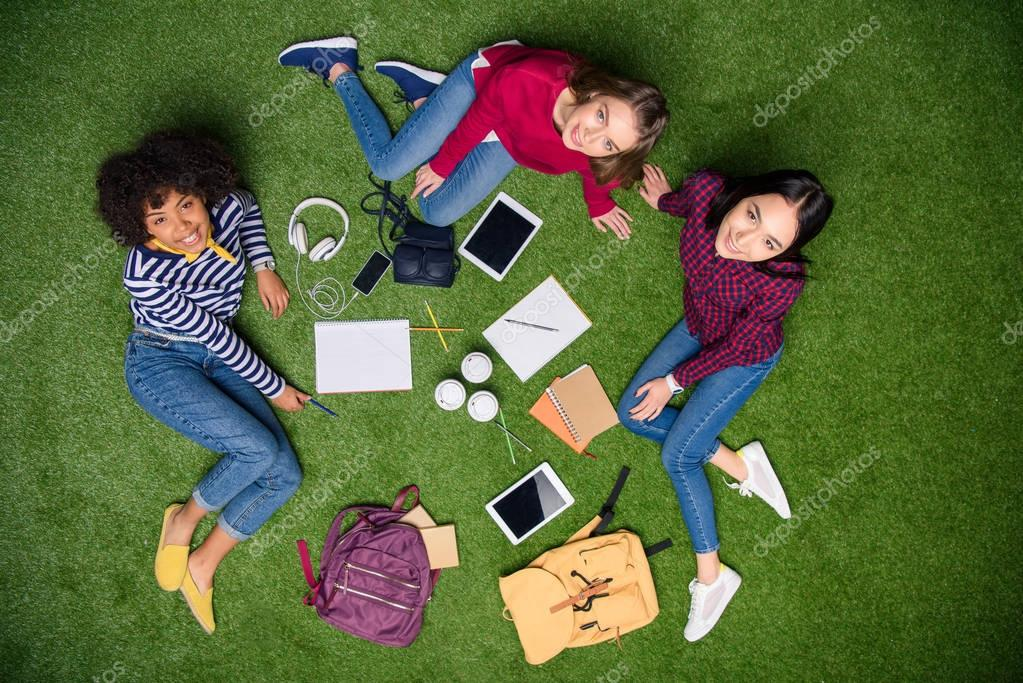 Overhead view of smiling multicultural students resting on green lawn stock vector